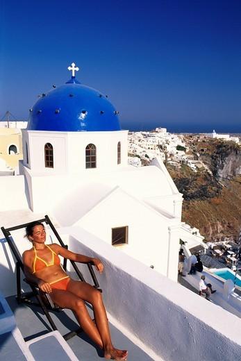 Woman lying on a deckchair on the terrace of a hotel near Thira, Santorini, Cyclades, Greece, Europe : Stock Photo