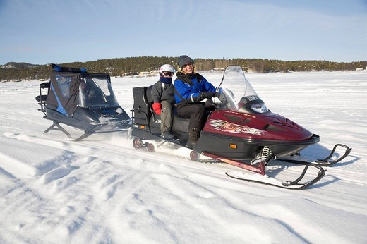 Woman, in her forties, and a girl, 6, on a snowmobile tour in Kiruna, Lappland, North Sweden, Sweden : Stock Photo