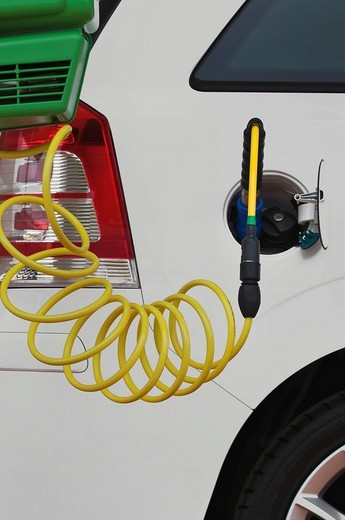 Fueling a passenger car with gas, gas pump nozzle in addition to a conventional fuel tank cap : Stock Photo