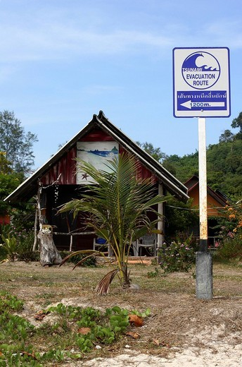 Tsunami danger sign and advice for evacuating people from the coast of the Andaman Sea in front of bungalow in South of Thailand, Asia : Stock Photo