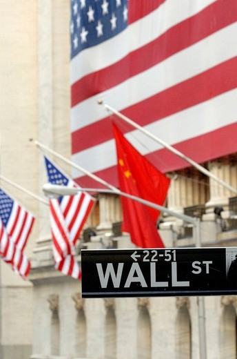 Wall Street, street sign in front of American flags, New York Stock Exchange, Financial District, Manhattan, New York City, NYC, New York, United States of America, USA : Stock Photo