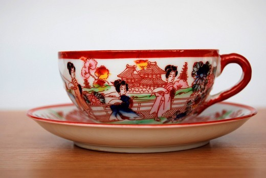 Stock Photo: 1848-184059 Asian tea cup and saucer made of fine handpainted porcelain with Japanese Geishas in front of a tea house as motive