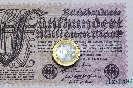 Old 500 Million Mark banknote and a one Euro coin, symbol for inflation : Stock Photo