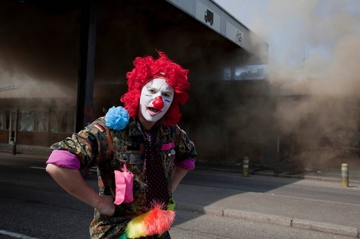 Stock Photo: 1848-184286 A protester disguised as a clown in front of customs building set on fire by protesters during protests against the NATO_summit, Strasbourg, France