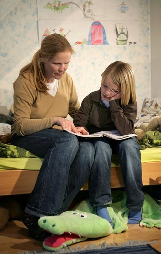 DEU, Germany: Mother is helping her son with homework for school. : Stock Photo