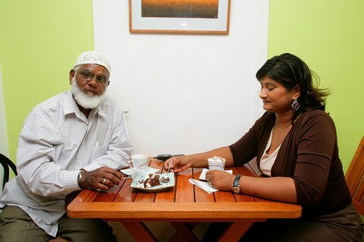 Two people of Indian ethnicity, patrons at a cafe in Georgetown, Guyana, South America : Stock Photo