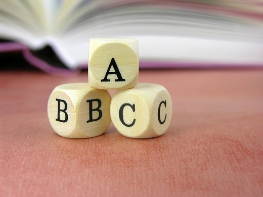 Stock Photo: 1848-185593 Three dice lettered ABC with open book in background