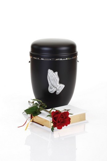 Stock Photo: 1848-185600 Black urn decorated with hands clasped in prayer, Bible and a red rose