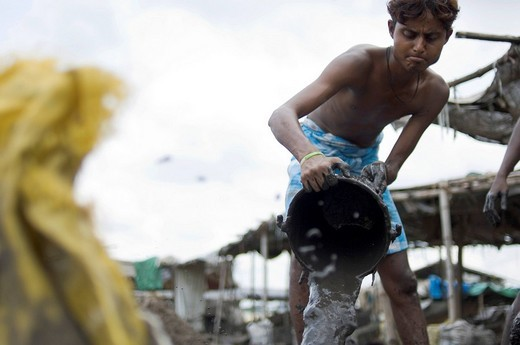 Many slum dwellers earn their income by recycling old industrial waste. Day labourers wash poisonous industrial slurry in the search for scrap metal. A young man pouring washed slurry into a dug_out hole. Howrah, Hooghly, West Bengal, India : Stock Photo