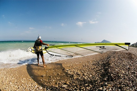 Windsurfer wearing helmet carrying his surfboard into the sea, Mediterranean coast, Spain : Stock Photo