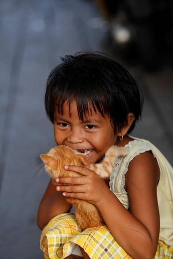 Girl holding a cat, Borneo, Central Kalimantan, Kalimantan Tengah, Indonesia, Asia : Stock Photo