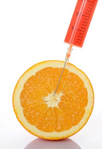 Syringe in an orange, symbol for genetically engineered food : Stock Photo