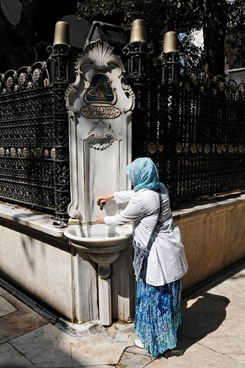 Devout Muslim woman filling water cups at the sacred fountain, the courtyard of the Eyuep Sultan Mosque, Eyuep village, Golden Horn, Istanbul, Turkey : Stock Photo