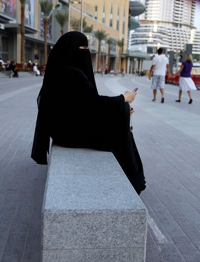 Arab woman in traditional black dress, the abaya, with cell phone, Dubai Mall, Dubai, United Arab Emirates, Middle East : Stock Photo