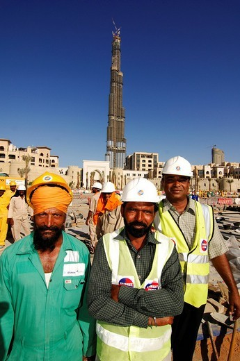 Construction workers in front of the highest skyscaper in the world, Burj Dubai, Dubai, United Arab Emirates, UAE, Middle East : Stock Photo
