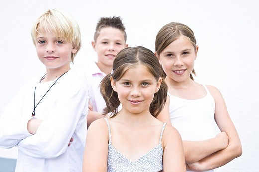 Four friends, arms folded, cool, in the schoolyard : Stock Photo
