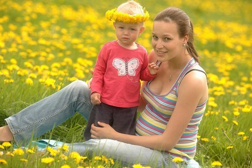 Pregnant mother and baby, girl, in a spring meadow : Stock Photo