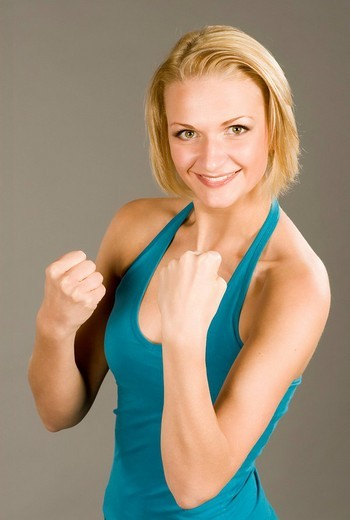 Young blonde woman posing like a boxer, smiling confidently at the camera : Stock Photo