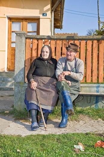 Romanian couple sitting on a bench in front of their house, Cernuc, Salaj, Transylvania, Romania, Europe : Stock Photo