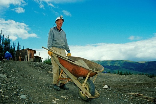 Stock Photo: 1848-195273 Prospector with wheelbarrow, pick and shovel on his way to work, Brooks Range, Alaska, USA