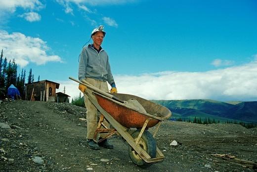 Prospector with wheelbarrow, pick and shovel on his way to work, Brooks Range, Alaska, USA : Stock Photo