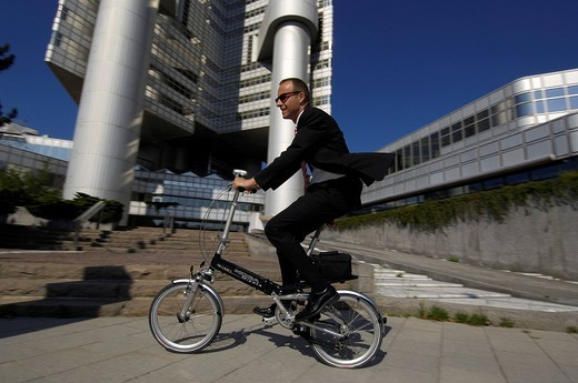Stock Photo: 1848-195956 Businessman on his way to work on a folding bike, Hypobank building, Bogenhausen, Munich, Bavaria, Germany, Europe