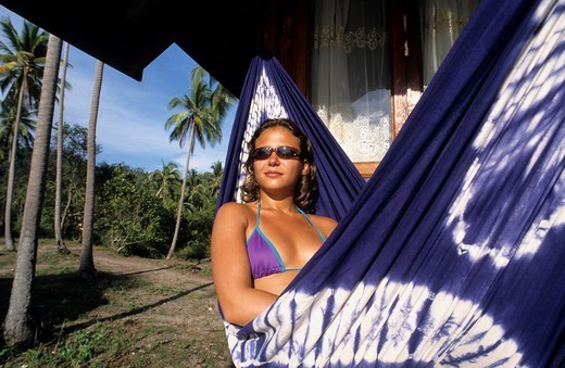 Stock Photo: 1848-196630 Young woman in a hammock under palm trees in front of a hut in the bay of Tong Nai Pan, Koh Pha Ngan Island, Thailand, Asia