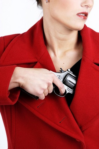 Young woman pulling gun from red coat : Stock Photo