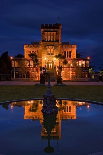Stock Photo: 1848-198153 Larnach Castle on the Otago Peninsula and its reflexion in the pond of a fountain illuminated by floodlight, New Zealand
