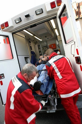 Stock Photo: 1848-19923 DEU Germany : Rescue paramedics first aid after an accident with a man injured at his leg. ambulance fire service. Training situation. ,