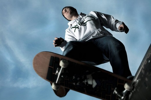 Stock Photo: 1848-199917 Young man on a skateboard about to spring to a hafepipe