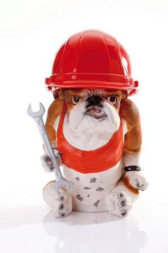 Bulldog figurine wearing a red construction helmet and holding a spanner : Stock Photo