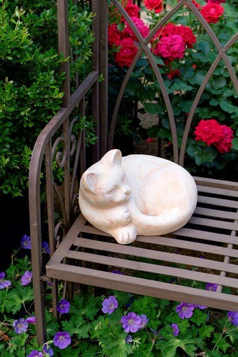 Garden deco, stone cat is lying on a metal bench in front of buxus, roses rosa and geranium : Stock Photo