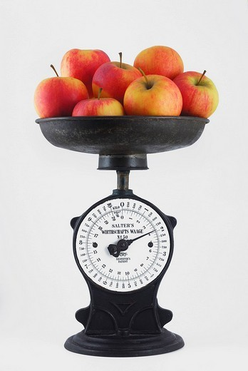 Antique iron kitchen scales with scale pan filled with almost 2 kg of apples : Stock Photo