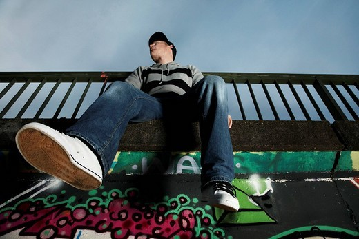 Stock Photo: 1848-203902 Young man sitting on a graffiti sprayed wall
