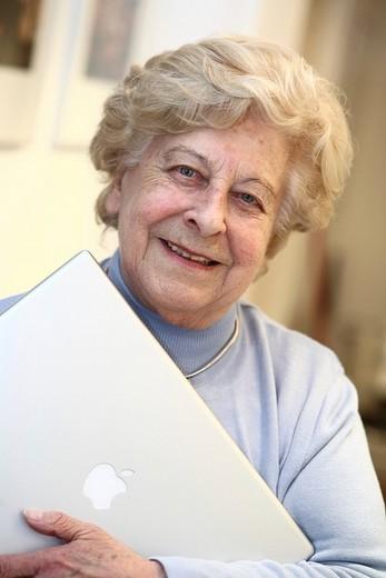 Stock Photo: 1848-205377 Senior woman holding a laptop