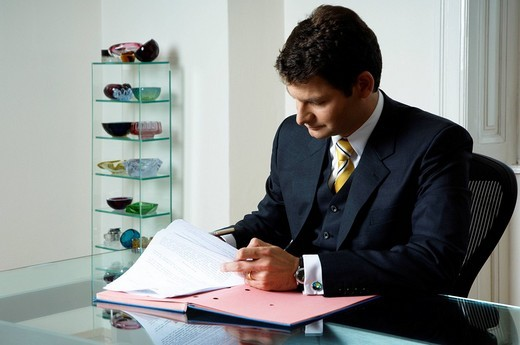 Lawyer, tax consultant, management consultant, reading and signing a file at a desk : Stock Photo