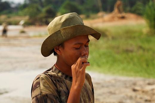 Boy smoking at a diamond mine in Cempaka, South Kalimantan, Borneo, Indonesia : Stock Photo