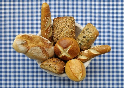 Bread, bread basket with various rolls on a red and white chequered table cloth : Stock Photo