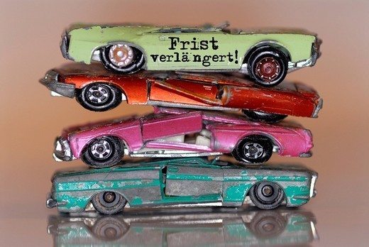 Broken miniature cars with lettering Frist verlaengert!, German for deadline extended, extension of the environmental bonus for the trading in of old cars when buying a new one : Stock Photo