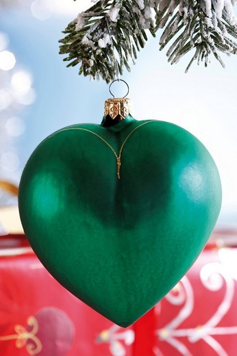 Green heart_shaped Christmas tree decoration on snowy fir branch : Stock Photo