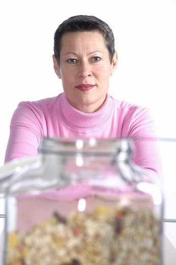 Woman at table with cereal jar : Stock Photo