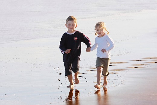 Boy, 4 years, and girl, 3 years, jumping and running hand in hand on the beach of Fuerteventura, Canary Island, Spain, Europe : Stock Photo