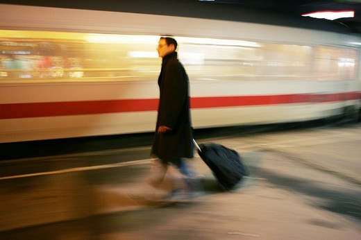 Stock Photo: 1848-216789 DEU Germany : Man on a platform of a railway station pulling his suitcase trolley while a Intercity train is passing by. ,