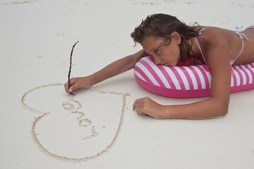 Stock Photo: 1848-218418 A lovesick girl, about 12 years, on holiday, is lying on an air mattress and painting a heart with the word love in the sand