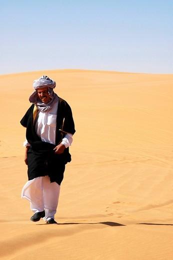 Arab man returns from the prayer in the desert, Sahara, Libya : Stock Photo