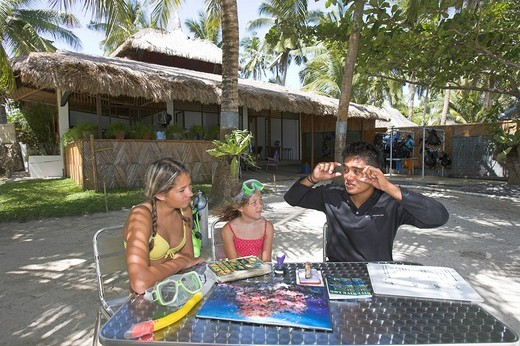 Diving teacher and two diving pupils in front of a diving school, Panglao, Philippines. : Stock Photo