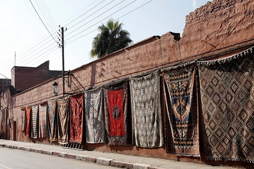 Colourful Berber rugs draped along a long wall in the historic Medina quarter, Marrakesh, Morocco, Africa : Stock Photo