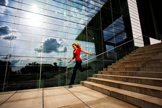 Stock Photo: 1848-221031 Young woman jumping down the stairs, Paul Loebe Haus, Berlin, Germany