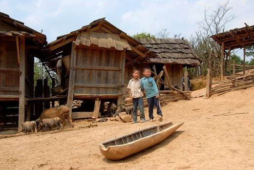 Two boys in a village of the Hmong Ethnie, remains of a bomb used as a feeding trough, Phakeo, Xieng Khuang Province, Laos, Southeast Asia : Stock Photo